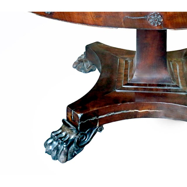 Antique round mahogany dining pedestal table with lion feet. Top of table has scratching,there are also stress cracks in...