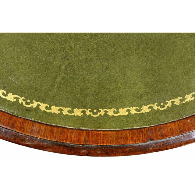 Circular with inset green leather top over drawers with ring handles, turned support ending on three saber legs and cup...