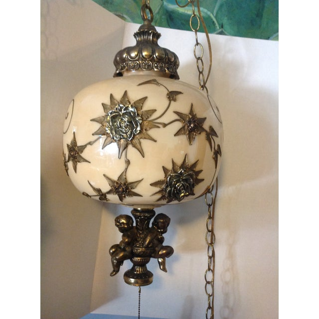 Hollywood Regency hanging light fixture with cherubs. This a very fancy gold and metal flowers on front with the carabs at...