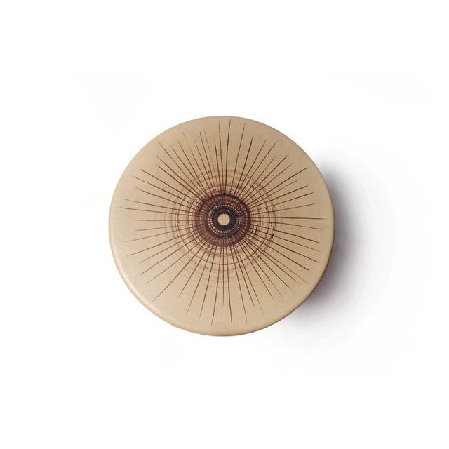 A mod occasional table comprising a circular ceramic top with concentric circle motif supported by a walnut cruciform...