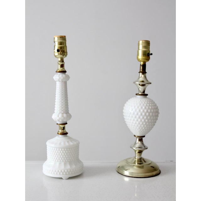 This is a pair of milk glass table lamps. The non-matching pair feature a hobnail pattern with chrome and gold hardware...