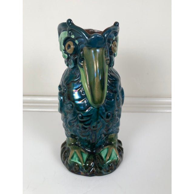 A Longpark English art pottery pitcher modeled as a bird in beautiful green, blue and brown glazes, with large eyes and...