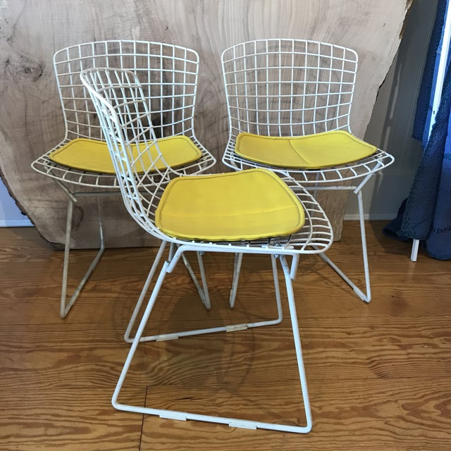 And original set of three Harry Bertoia child size chairs in white, with yellow vinyl cushions. Model 426. Made from...