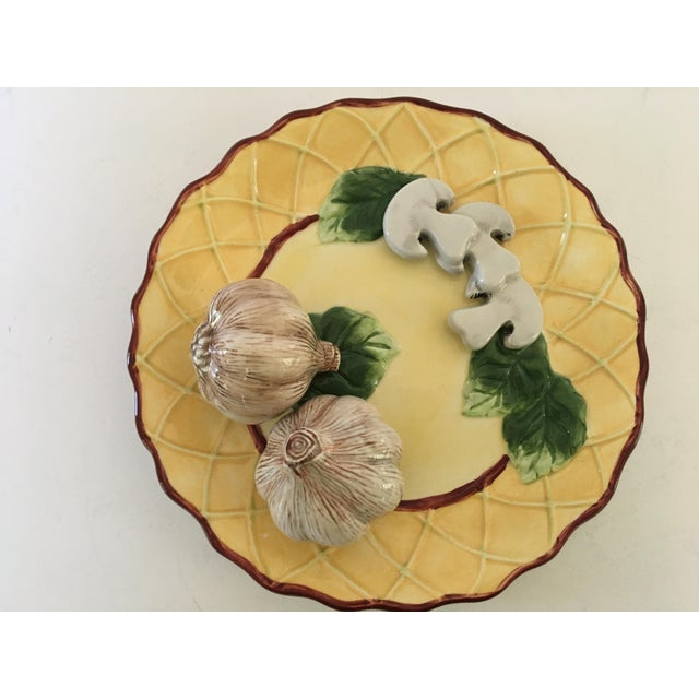 Offering a decorative Trompe l'Oeil painted scalloped plate. Adorning this dimensional plate are two garlic bulbs and...