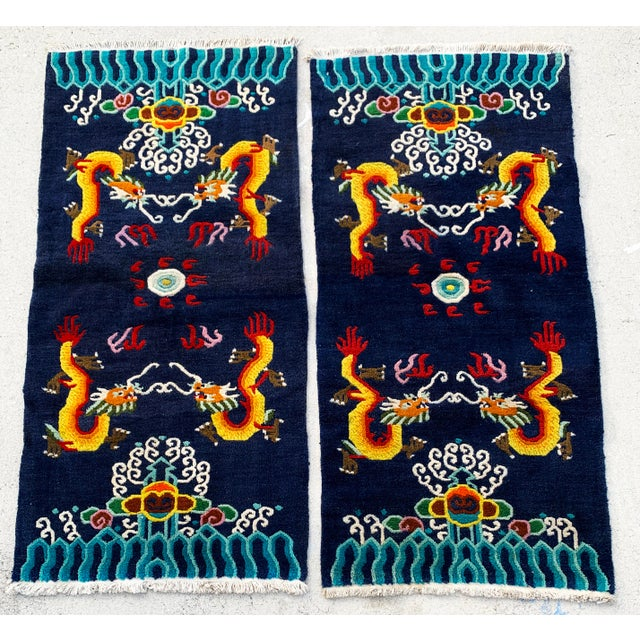 Magnificent pair of vintage hand knotted Chinese wool rugs with a dragon motif. This is a rare find a pair both in...