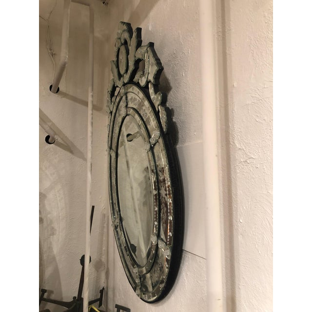 A super glam oval Venetian style ornate mirror with pretty etched decoration and elaborate curlicues and foliage at the top.