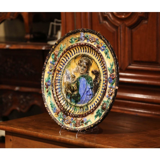 Decorate a wall with this antique and colorful barbotine platter; crafted in Italy, circa 1920, the large charger features...