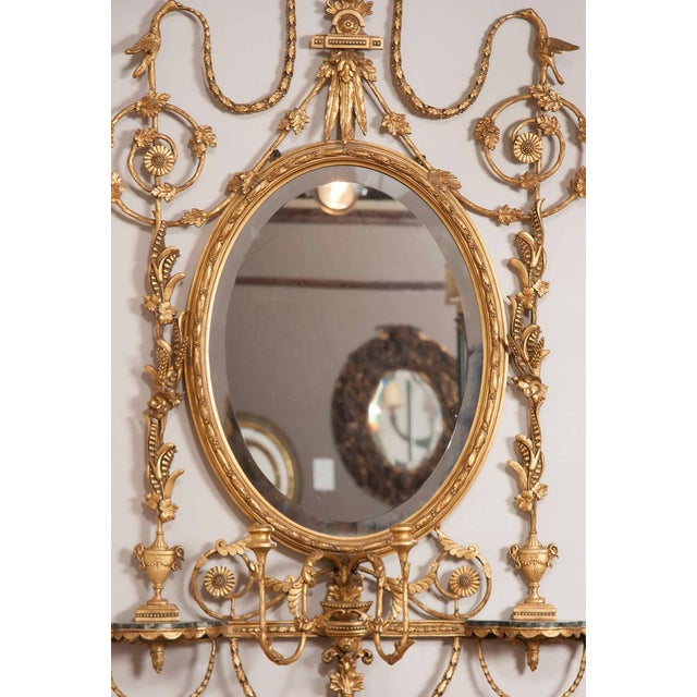 In the style of Robert Adam. Urn form finial with leaf tip swags and scrolls over an oval beveled mirror and a pair of...