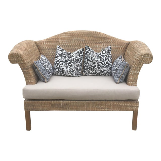 Hand woven natural rattan settee. The blended mixture of natural rattan colors create an organic trend following sought...