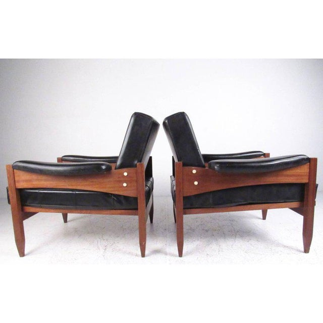 This stylish pair of Mid-Century club chairs feature tufted vinyl upholstery with sturdy teak frames. The vintage modern...