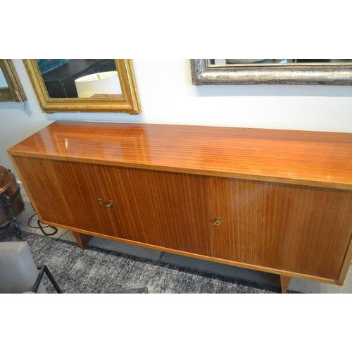 Fabulous mid-century sideboard from France, c.1960s. Features a beautiful light mahogany veneer and three drawers and...
