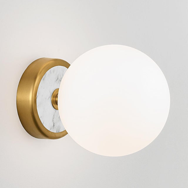 Brushed brass wall lamp with natural stone and opal glass. The glass globe is secured with a threaded metal ring to ensure...