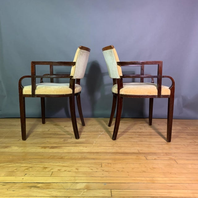 Perfectly proportioned pair of Art Deco period armchairs with architectural arm structure and frame in mahogany. Shaped,...