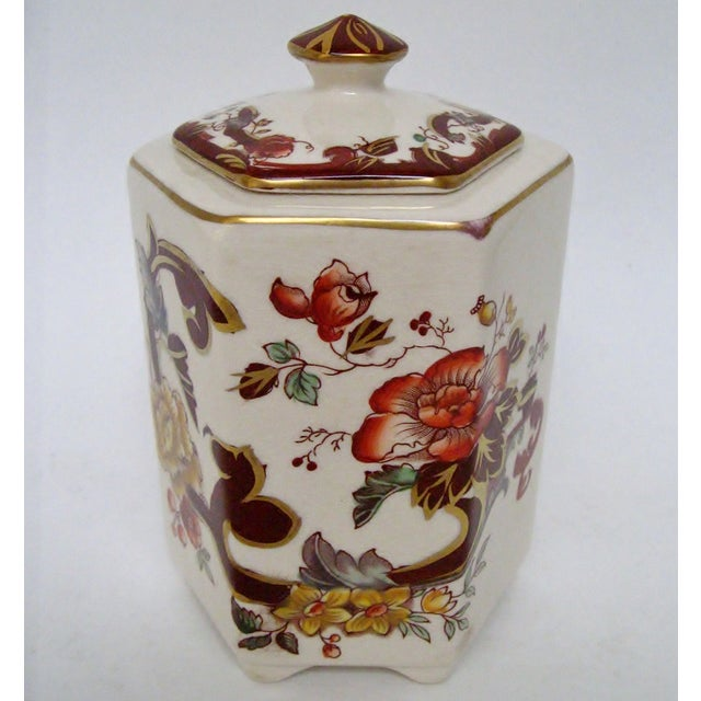 Vintage English earthenware footed tea caddy in hexagonal shape with hand-painted floral design in brown velvet pattern....