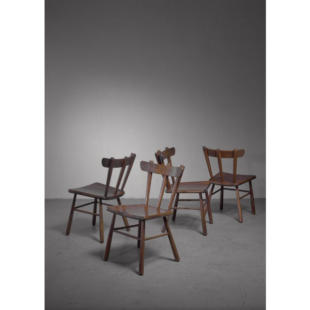 A set of four Scandinavian Modern wooden dining or side chairs with rounded legs and a curved spindle backrest. We also...