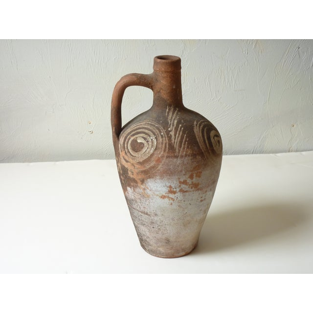 Primitive jug with painted swirls, looks like archaic pottery, possibly Turkish.
