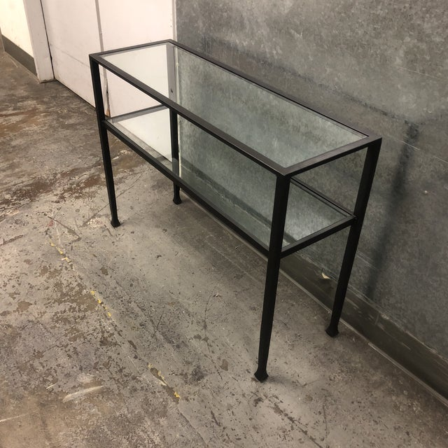 Design Plus gallery has an Iron and glass console table. The Iron frame has a Black painted finish, most of the interest...