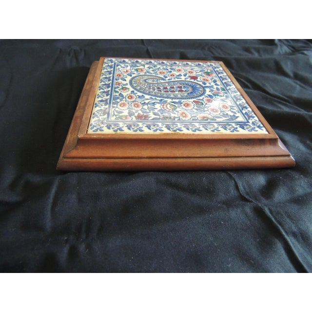 Hand painted paisley ceramic Persian tile trivet inset in wooden frame with wooden backing. In shades of blue, natural,...