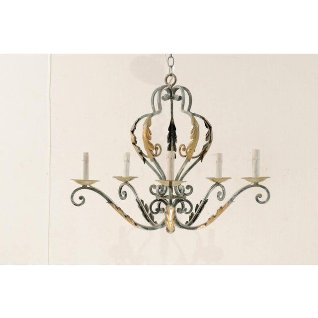A French vintage five-light painted iron chandelier. This French iron chandelier from the mid-20th century is adorned in...