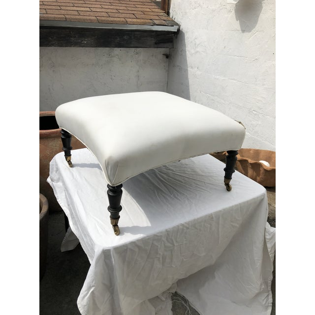18th century white upholstered ottoman with dark carved wood base on wheels. While there is some damage and staining to...
