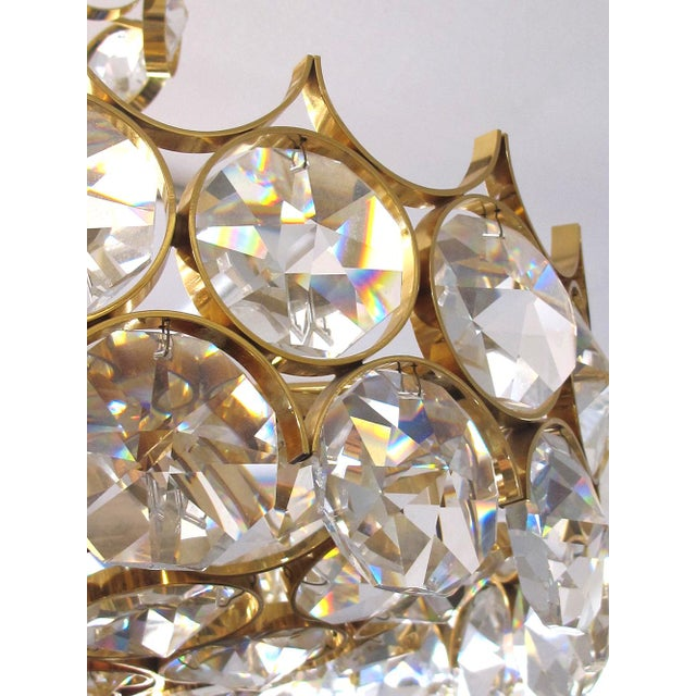 this stylish Hollywood Regency gilt-brass and crystal pendant light fitted with over-scaled round faceted crystal elements