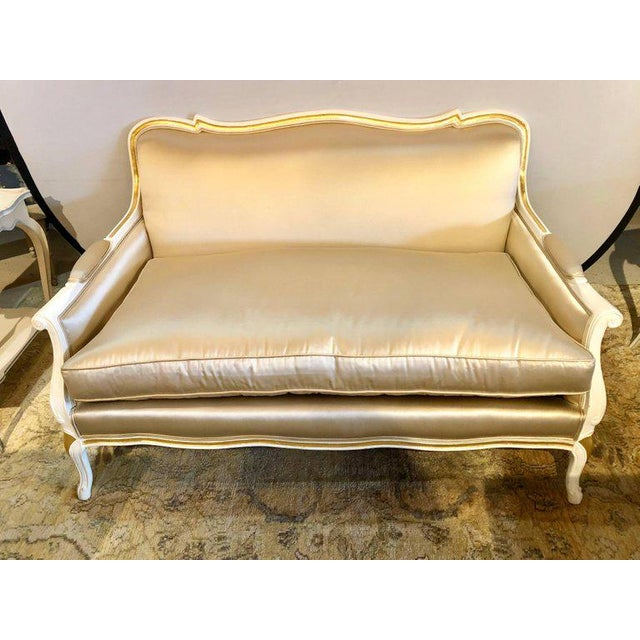 A gilt and paint decorated settee / loveseat in a fine satin upholstery. In this Louis XV style this fine Hollywood...