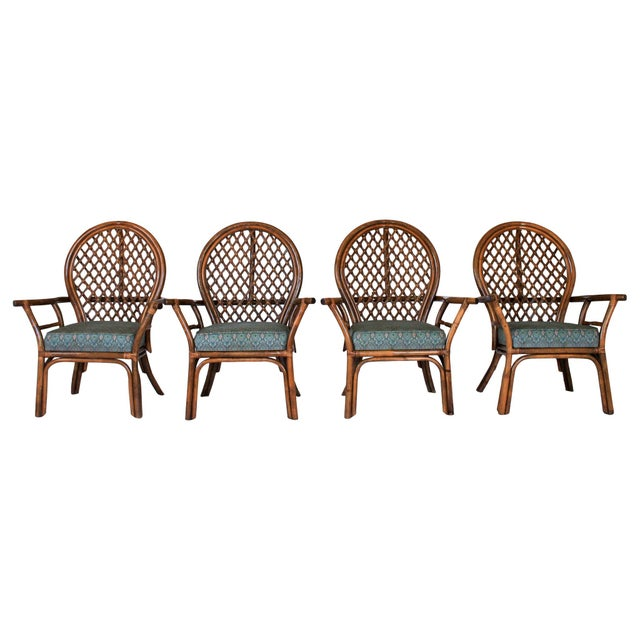 Set of four vintage rattan fan back dining chairs with attached cushions. No makers mark. Some light soiling and wear to...