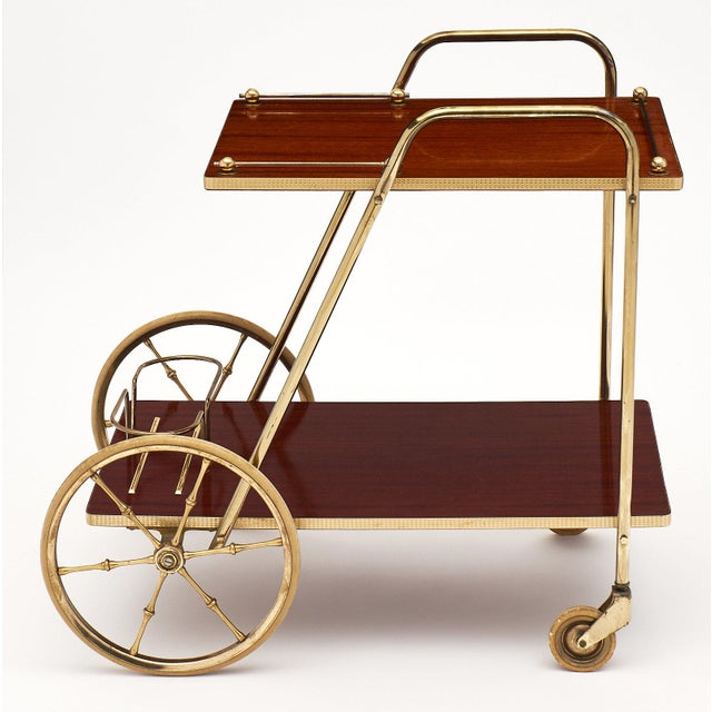 French Art Deco period rosewood and brass bar cart. This fun bar cart of rosewood veneer features a striking brass...