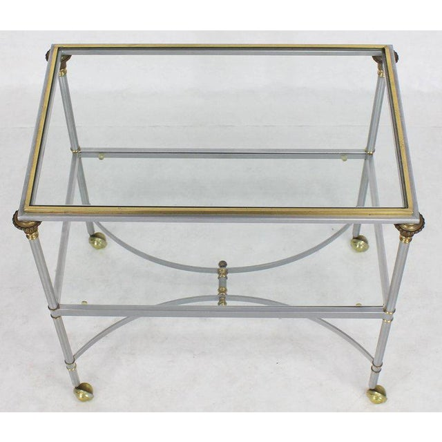 Brushed chrome brass finials glass shelves serving cart side table on wheels. Made in the mid 20th century.
