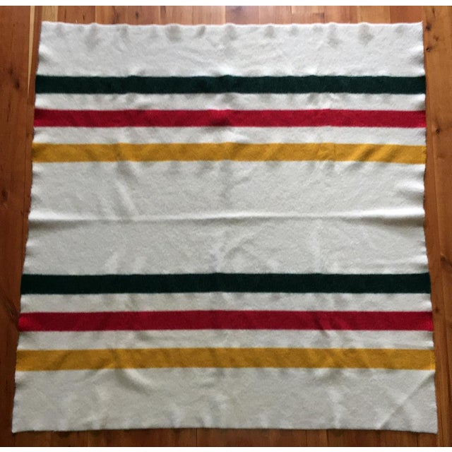 Timeless wool three stripe design blanket to use at the foot of bed or over a couch or chair. Warm white blanket has three...