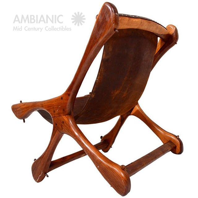 DESCRIPTION: For your consideration a sling chair with sculptural wood frame and old leather sling. Leather attached by...
