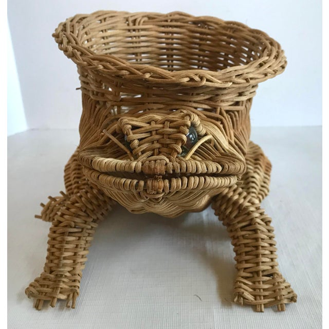 This cute vintage frog shaped planter basket has glass eyes.