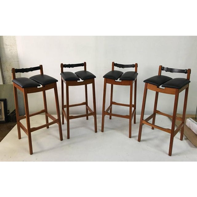 These vintage bar stools feature masculine lines, a black leather worn belt strap as a backrest and newly upholstered...