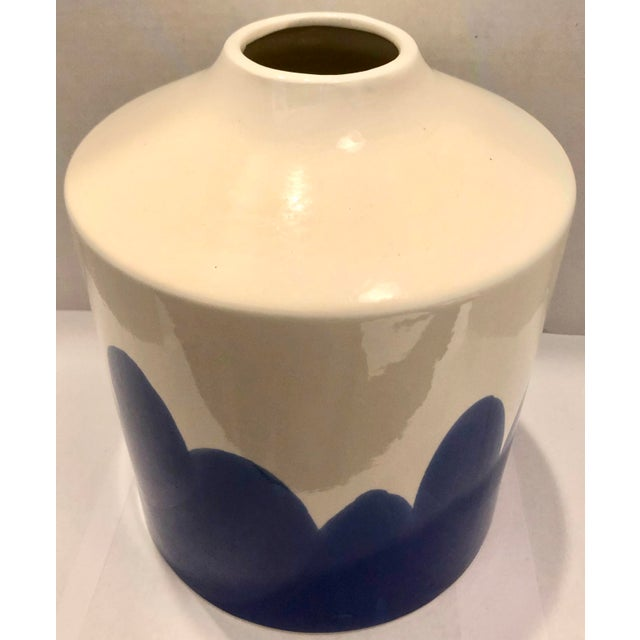 Sleek and interesting fat ceramic vase. White body with blue pattern. Very decorative.