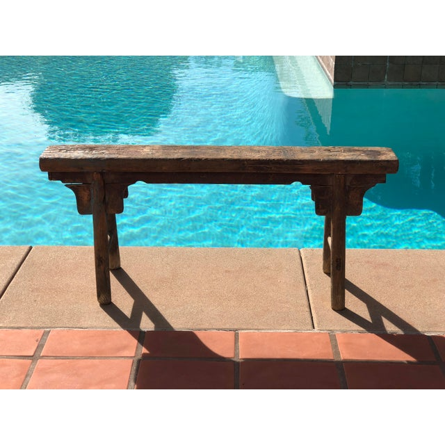 Antique faded barn red Shandong hand-crafted bench is constructed of solid elm using mortise and tenon joinery and shows...