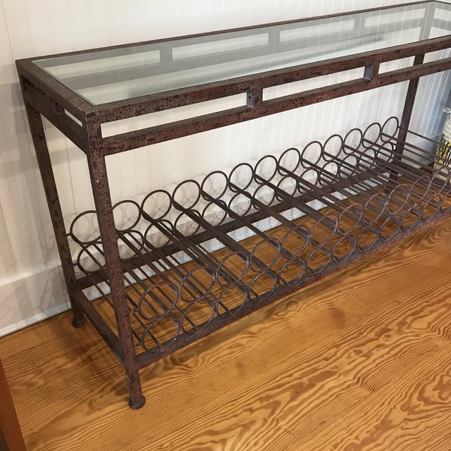 Custom hand-forged wrought iron console table with squared legs, a wine rack and glass top. Holds up to 26 bottles below....