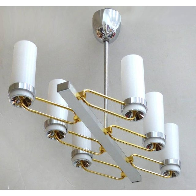 A very unusual Mid-Century two-tone chandelier with six brass and silver tone angled arms that each support a white glass...
