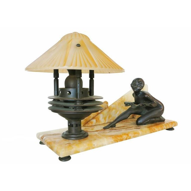 Art Deco styled desk lamp with a decorative Italian Crema Valencia marble base and bronze lamp. The lamp features a bronze...