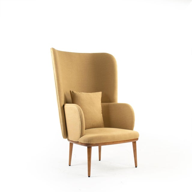 Wing back occasional chair with khaki linen upholstery, four straight legs, and 20 x 20 throw pillow.