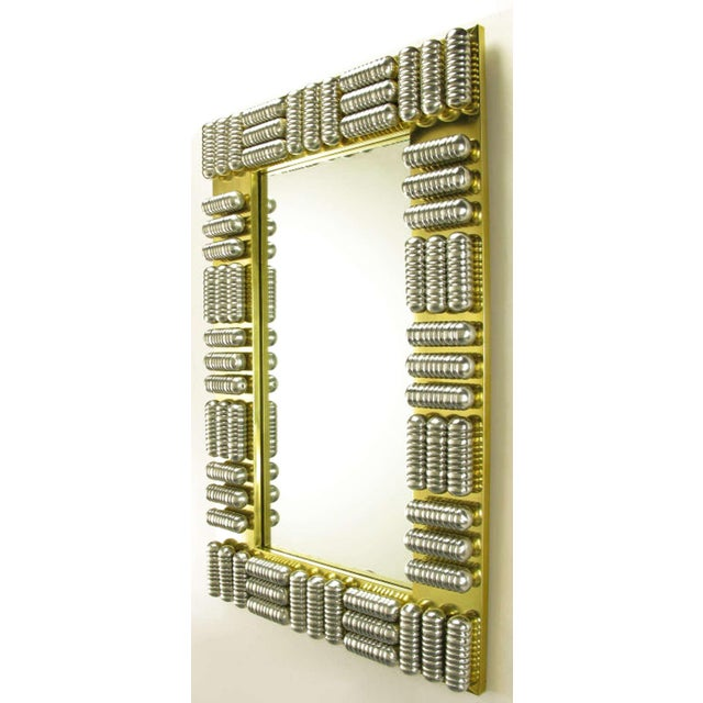 Custom made wall mirror with brass wrapped wood frame and a series of polished and ribbed aluminum enclosed tubes. Each...
