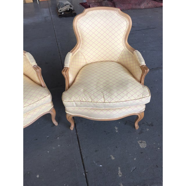 Pair of Classic French Begeres with light wood frames, upholstery and wood is in excellent condition. The color of the...