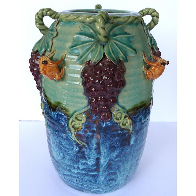 A large handled Majolica vase decorated with dimensional grapes, leaves, and frogs. Rich glaze tones and great detail.