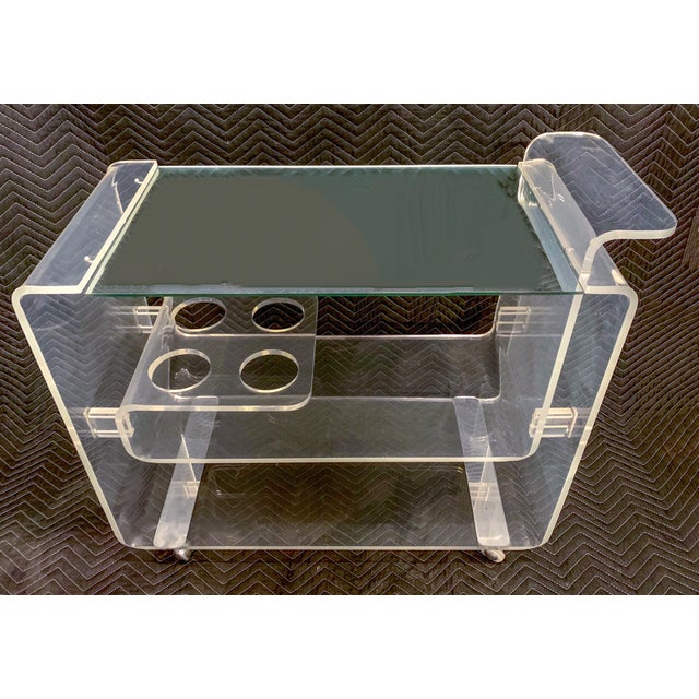 This lucite bar cart has a removable mirrored top, center shelf bottle holders and continuous bent lucite. It was...