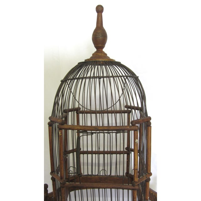 Charming antique wood and wire birdcage featuring a hanging swing in the top portion, two adjustable troughs for food and...