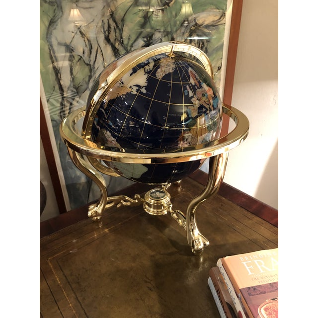 Absolutely beautiful tabletop globe having inlaid pieces of multi colored stone and a solid brass base.