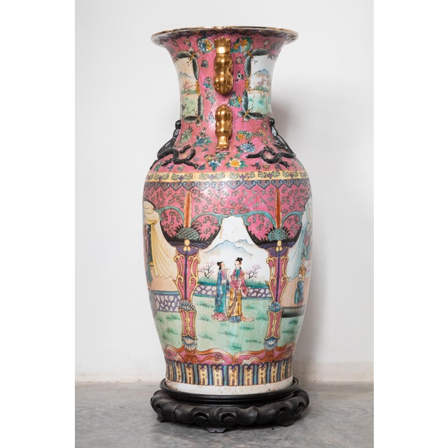 Large Antique Chinese Canton vase on a carved wooden base. Features handpainted scenes of tea ceremonies, figures in a...