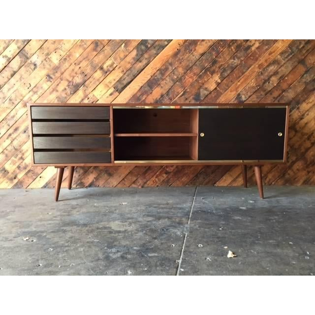 Mid-century style custom walnut and brass credenza. Features brass trim, four drawers, and plenty of storage with shelves.