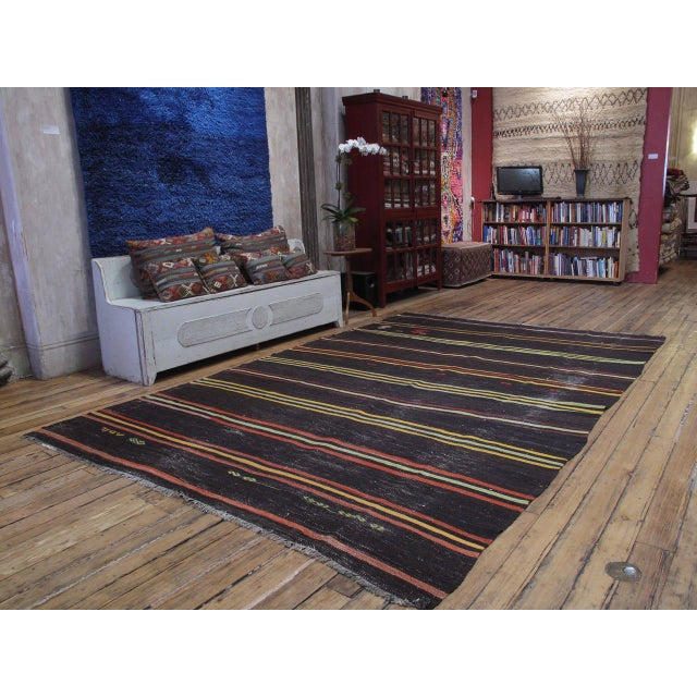A large tribal floor cover from Southeastern Turkey, woven with tightly spun, dark brown goat hair, decorated with...