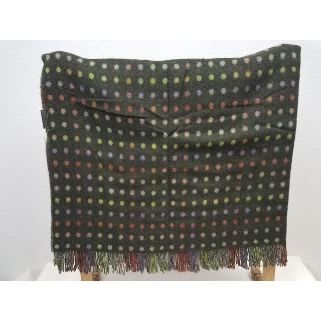 A fun and versatile throw in a reversible spot design made from soft 100% Merino lambswool. The colors are greens, reds...