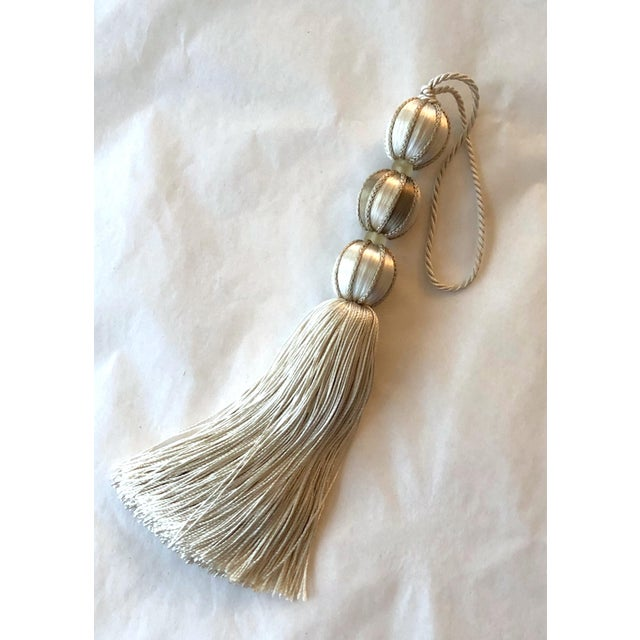 Ivory and taupe beaded key tassel connected by a twisted cord that loops through three satin covered beads. Taupe colored...